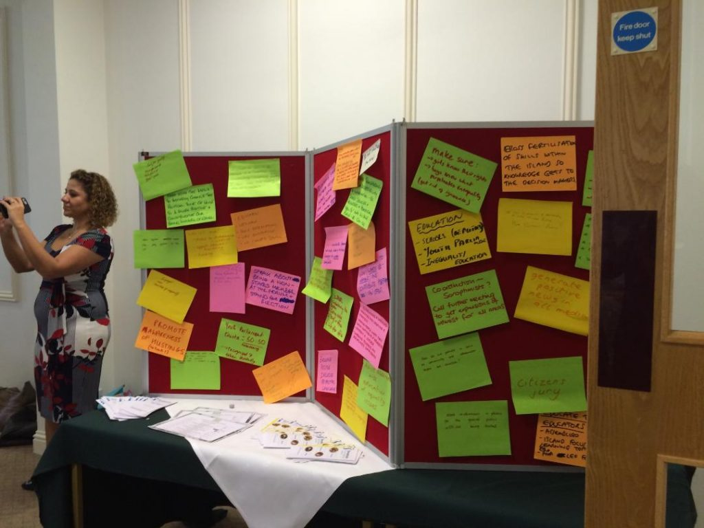Three-panel pinboard covered in Post-It notes standing on a table