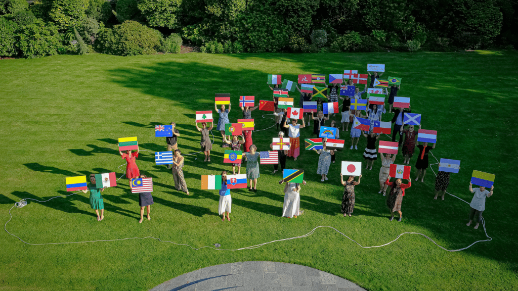 People holding up country flags inside a rope outline of Guernsey.